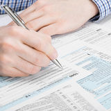 United States of America Tax Form 1040 - man performing tax calculation - 1 to 1 ratio Stock Photo