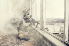 United States Army rangers in action. United States Army rangers during the military operation in the smoke and fire Royalty Free Stock Photo