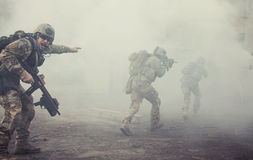United States Army rangers in action. United States Army rangers during the military operation in the smoke and fire Royalty Free Stock Photos