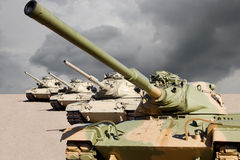 United States Army War Tanks in the Desert. Four United States army war tanks ready for battle with dark cloudy skies and dry desert sands background Stock Images