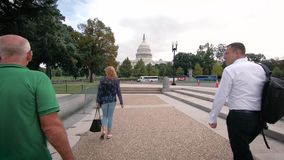 The United States Capitol building. September 15, 2018. Washington DC, District of Columbia, USA. Two men go to The United States Capitol building. Autumn stock footage