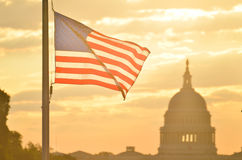 United States Capitol building and US flag silhouette at sunrise, Washington DC