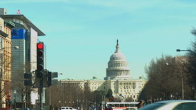 United States Capitol Hill. Distant long shot of the United States Capitol Building in Washington D.C. with traffic and pedestrians passing in the foreground stock video