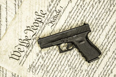 United States constitution and gun rights. A handgun symbolizing gun rights while framed against the United States constitution stock image