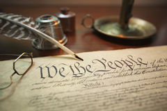 United States Constitution with quill, glasses and candle holder. Selective focus image of the United States Constitution with quill pen, glasses and candle Royalty Free Stock Image