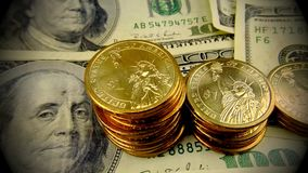 United States Currency Gold Coins and One Hundred Dollar Bills. American currency gold coins stacked on top of one hundred dollar bills - Finance and banking stock footage