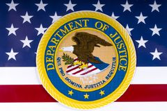 United States Department of Justice. LONDON, UK - MARCH 26TH 2018: The symbol of the United States Department of Justice portrayed with the US flag, on 26th Royalty Free Stock Photo