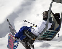 United States Extreme Winter Cold and Snow. A trio of skiers and snowboarders ride in a winter snow ski hill chair lift at Sunrise Ski Resort in the White Stock Photography