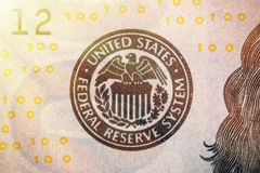 United States Federal Reserve System symbol from hundred dollar bank note. Close up shot with sun beams effect.  Stock Photos