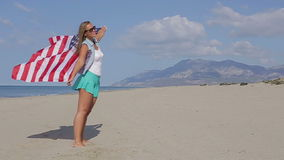 United States Flag. Beautiful girl on the ocean Slow mo stock video