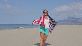 United States Flag. Beautiful girl on the ocean Slow mo stock video footage