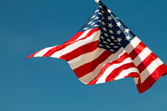 United States flag blows in the wind against a blue sky attached to the wall from the side. Royalty Free Stock Photo