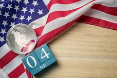 United states flag with crystal glass globe and wooden calendar on wood background stock photos