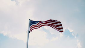 United States flag flying from a flagpole. United States American flag flying from a flagpole in a wind showing the stars and stripes against a cloudy blue sky stock footage