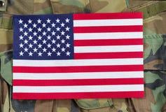 United States flag with military background. Top view angled shot of United States flag with military uniform background Royalty Free Stock Photos