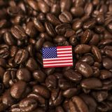 A United States flag placed over roasted coffee beans stock photography