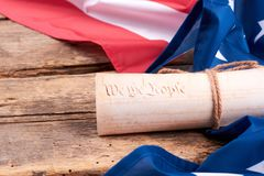United States flag and rolled-up Constitution. stock photo