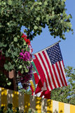 United States Flag Surrounded by Flowers Trees and Blue Sky Stock Images
