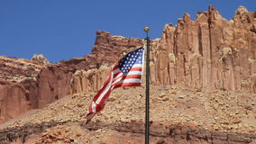 United States Flag. Waving against huge mountains stock footage