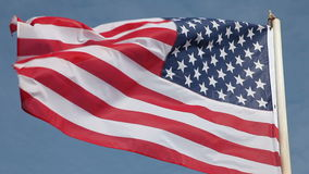 United States flag waving in wind. Against clear blue sky stock footage