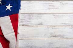 American flag on a white worn wooden background with copy space. United states flag on white, weathered clapboard background with copy space royalty free stock photos