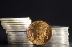 United States Gold Buffalo infront of SIlver Coins. On black background stock photography