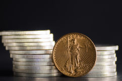 United States Gold Eagle Coin Saint-Gaudens infront Silver Coins.  royalty free stock photo