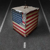 United States Government Shutdown. Roadblock obstacle and barrier business concept with a huge cement or concrete cube with an old American flag blocking a road Royalty Free Stock Photography