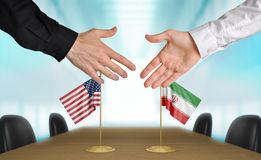 United States and Iran diplomats agreeing on a deal. Two diplomats from the United States and Iran extending their hands for a handshake on an agreement between Stock Photography