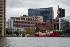 United States lightship Chesapeake historic ship docked in Baltimore Inner Harbor with stores and National Aquarium stock photos