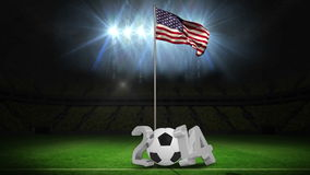 United States national flag waving on flagpole with 2014 message. On football pitch with flashes stock video