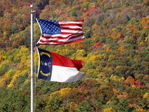 United states and north carolina flag. Old glory and north carolina flag flying in stiff wind against beautiful autumn blue ridge mountains stock image