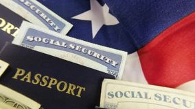 United States passport and currency with social security card - Travel documents tourism concept. United States passport, American flag one hundred dollar bills stock video footage