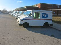 United States Postal Service Trucks Parked in Parking Lot. A lot of USPS postal trucks are parked in the parking lot as they are off service Royalty Free Stock Photo