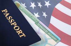 United States resident card, immigration concept. United States of America permanent resident card, green card, displayed with a US flag in the background and a Stock Image
