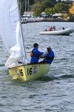 United States Sailing team. Sailboat leaves the harbor as the race official watches at the United States Sailing Associations Championship of Champions Title at Stock Photos
