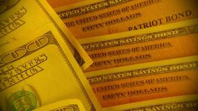 United States Savings Bonds with American Currency. Financial Security - United States Treasury Savings Bonds with One Hundred Dollar Bills stock footage