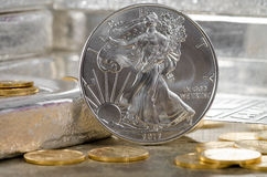United States Silver Eagle with Gold coins & silver bars in background.  stock photo