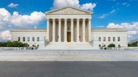 United States Supreme Court Building at summer day in Washington DC, USA. United States Supreme Court Building and American flag at sunny day in Washington DC royalty free stock photography