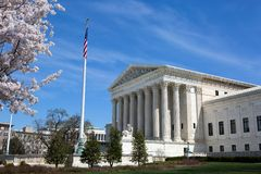 United States Supreme Court. Building and grounds with US Flag and cherry blossoms on tree Stock Photo