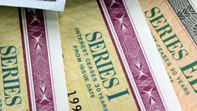 United States Treasury Savings Bonds with One Hundred Dollar Bills. United States Savings Bonds with American Currency - Banking and Financial Security concept stock video