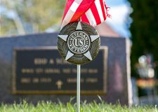 US Veteran Marker in Cemetery. United States Veteran cemetery marker with American flag stock photos