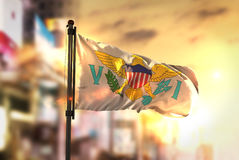 United States Virgin Islands Flag Against City Blurred Background At Sunrise Backlight. Sky royalty free stock photos