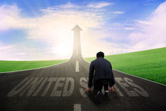 United States word with businessman on road. Image of businessman kneeling on the road with United States word while looking at road shaped upward arrow Stock Image