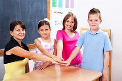 United students and teacher. Group of united students and teacher, putting their hands together Royalty Free Stock Image