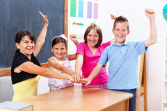 United students and teacher. Happy winner group of united students and teacher in school, raising and holding hands together royalty free stock photo