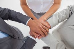 United team piling up their hands. In the workplace Stock Photos