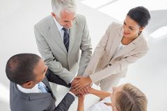 United team standing together and piling up their hands. In the workplace Stock Images