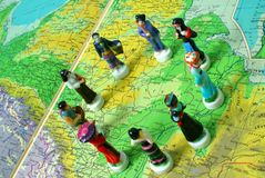 Unity. Porcelain figurines on map Royalty Free Stock Photography