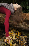 Unity. Beautiful young woman laying on a tree trunk touching fallen leaves Stock Photography